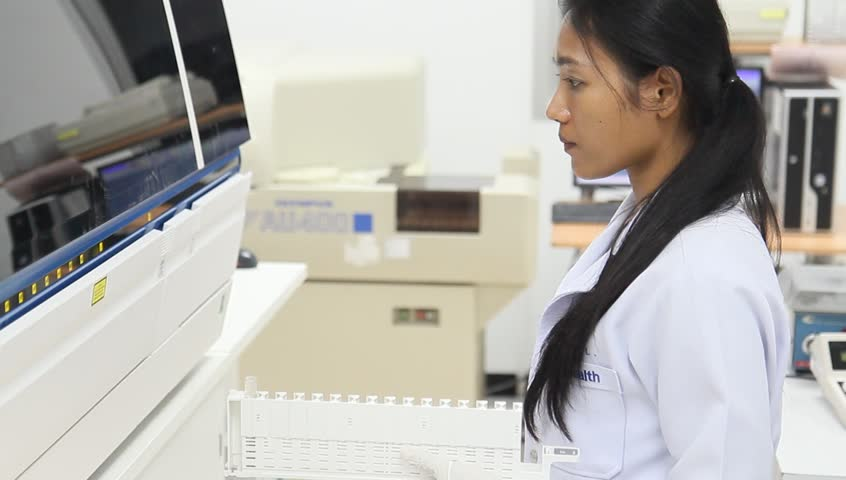 Woman working in the modern medical laboratory. Medical staff working on the analysis of blood samples. Research and test of blood in a hospital. The doctor examined blood samples.