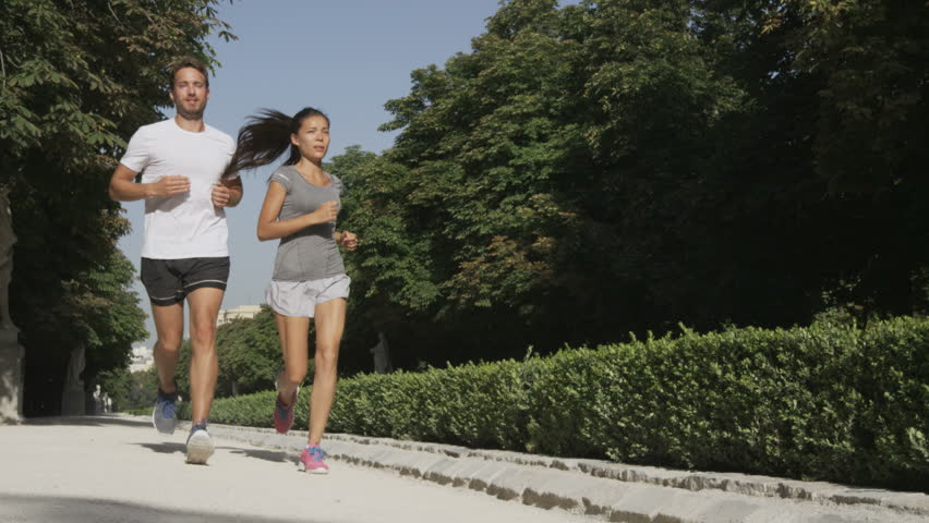Sport couple running jogging in city park. Runners exercising - woman and man runner training on run living healthy active lifestyle in Retiro Park in Madrid, Spain, Europe. RED EPIC SLOW MOTION.