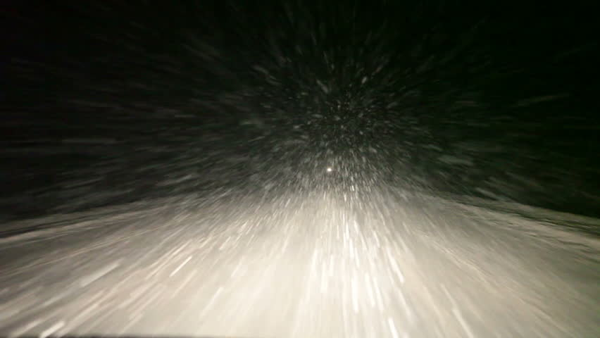 Night road with strong blizzard in moving car headlight, winter, pov, loop. Northern Russia