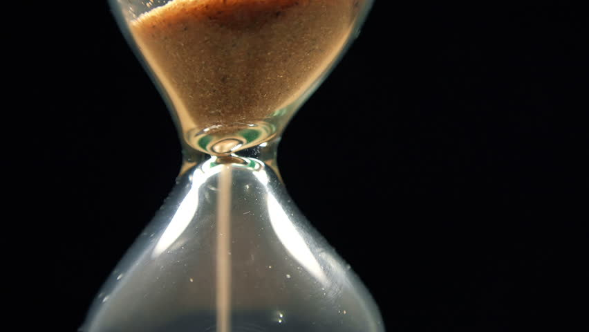 Close-up View of Sand Flowing Through an Hourglass on black background. 4K Ultra HD 3840x2160 Video Clip