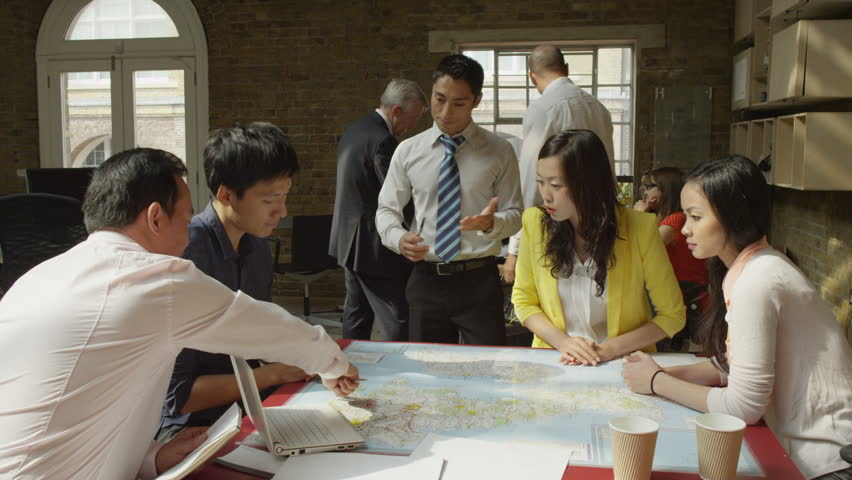 4K Asian business team in strategy meeting, looking at a map of the world | Shutterstock HD Video #8739439