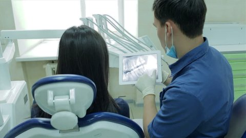 At a reception the dentist. The girl in the dental chair. Dentist shows a patient x-ray on the tablet of her teeth