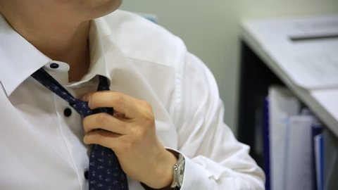 Tired businessman working late at night and loosening his tie in the office