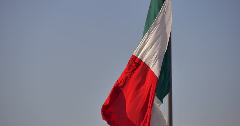 MEXICO CITY - CIRCA FEBRUARY 2015 - An enormous Mexican national flag flying high over Chapultepec Park in Mexico City. A helicopter flies by in the background.