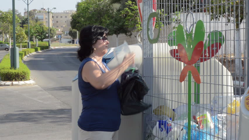 Let's keep our planet clean drop plastic bottles into a special bin. Woman is throwing away used plastic bottles to cell recycling container outdoor.