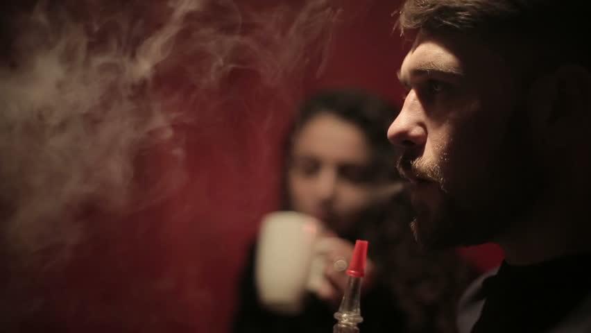 Couple smoking shisha or hookah in cafe. Close up.