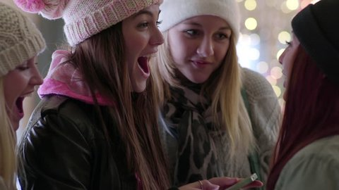 Group Of Multi-Ethnic Teens Look At Embarrassing Photo Of Their Friend On A Smartphone, They All Laugh (Slow Motion, Bokeh Lights In Background)