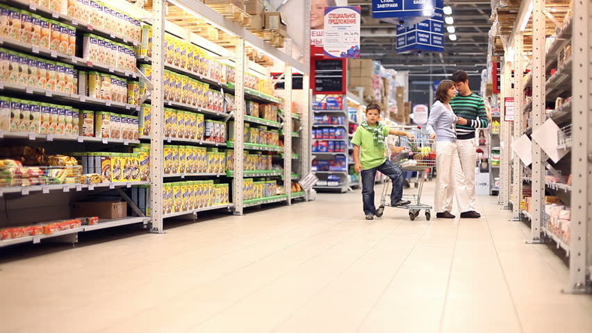 Two parents and their sons choosing groceries and putting them into the trolley. The other son approaching them and calling his brother to go with him | Shutterstock HD Video #885961