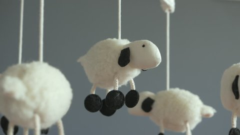 Lamb Nursery Mobile spinning above Baby Crib, Close-Up