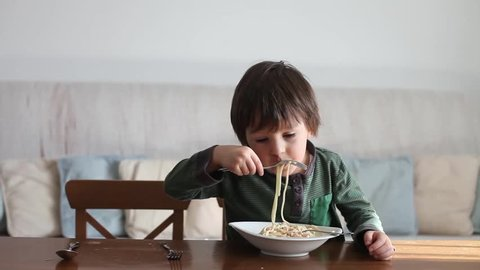 Adorable little boy, eating spaghetti at home, homemade pasta