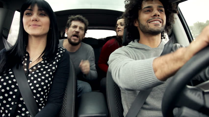 friends in car singing and dancing like crazy