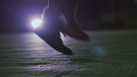 4K Camera pans up in slow motion of someone skipping at night, shot on RED EPIC