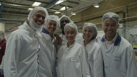 4K Production facility team staff together on factory floor. Smiling men and women working together.