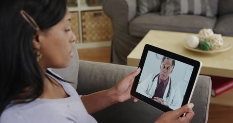 Senior black woman patient listening to doctor talk on tablet