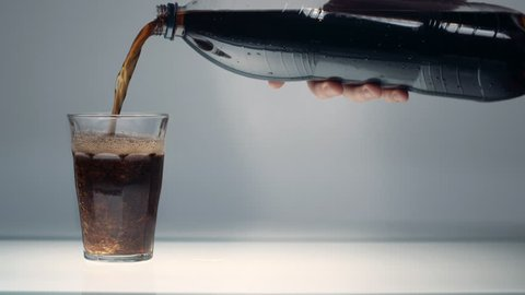 Pouring coke/cola/soda into a glass on a table in a clean, studio environment.