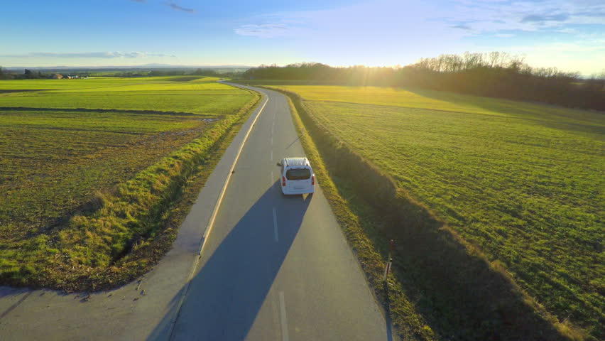 Aerial of green countryside and car driving through 4K. Flying behind and beside a white car vehicle driving though green nature with sunset shining and making long shadows of car.