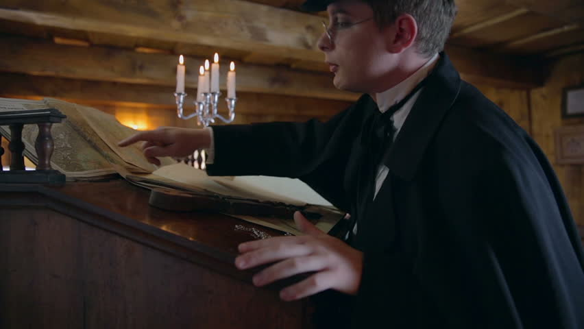 The polities from Middle ages examine the old maps . Close up footage of a man from medieval times examine the old maps on the wooden vintage table on the old house.