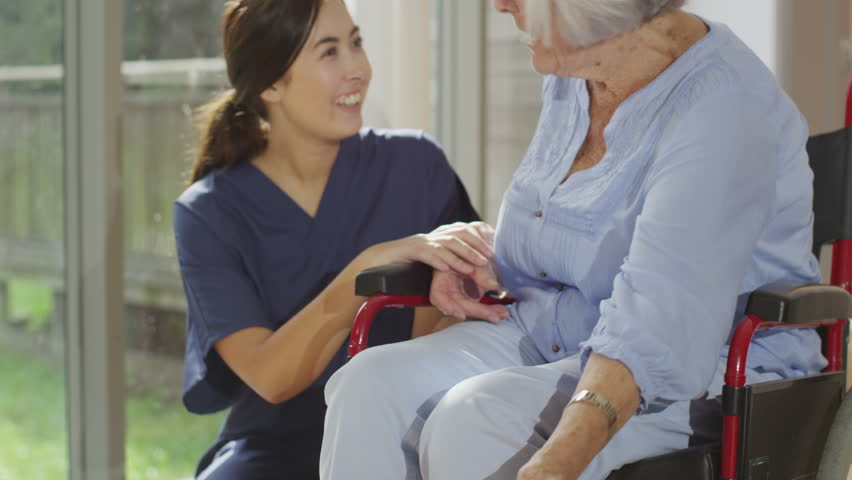 4K Caring nurse giving support to elderly female patient in a hospital or residential care home