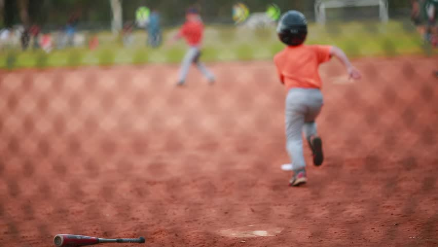 Shot of Unrecognizable Kid Running the bases at a Baseball Game. At the end of the shot you can see a game of soccer in the back.