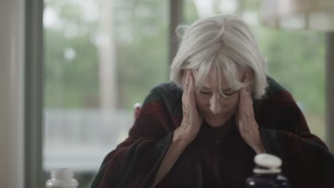 4K Portrait of sad senior lady confused about which medication to take