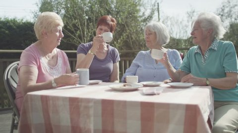 4K Group of cheerful senior female friends chatting in the garden with cups of tea. They raise cups for a toast and kiss each other on the cheek.