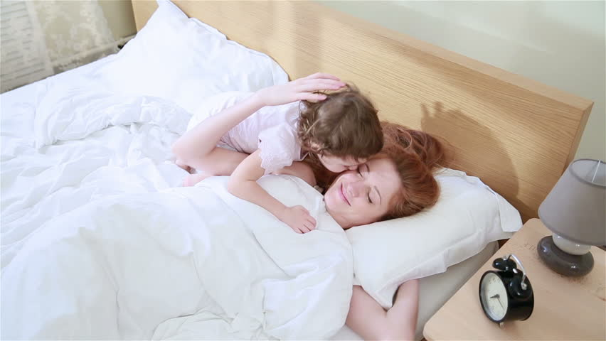 Cute little girl wakes up her young mother in the early morning, hugs and kisses.