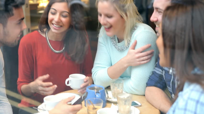 Group of friends sit around table in cafe - drinking, talking and using mobile phones. Shot on Sony FS700 at a frame rate of 25fps