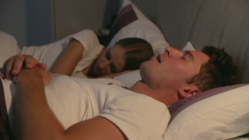 Couple lying in bed - woman is disturbed by man snoring so she shakes him.Shot on Sony FS700 at a frame rate of 25fps