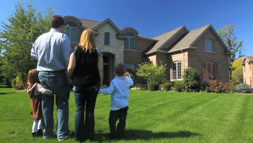 A family stands together in their yard, facing their luxury home