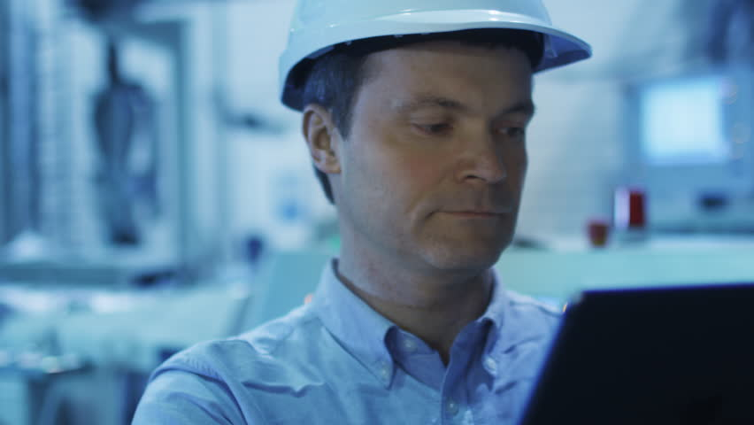 Engineer in Using Tablet in Factory. Shot on RED Cinema Camera in 4K (UHD). Its easy scale, rotate and crop without loosing quality.