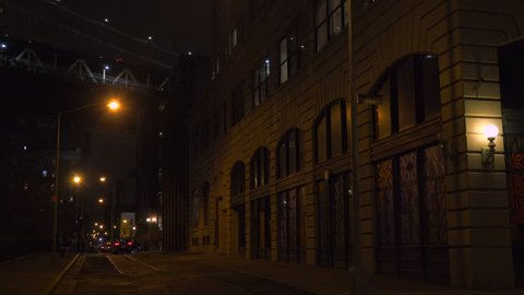 NEW YORK CITY - CIRCA 2015 - Establishing shot of warehouses under the Brooklyn Bridge with subway train crossing.