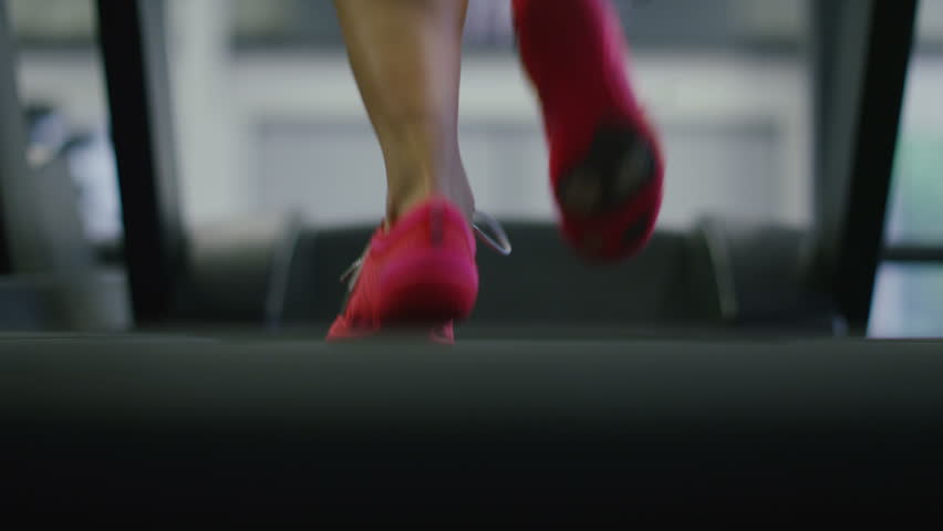 4K Camera tilts up on a young woman running on a treadmill, shot on RED EPIC