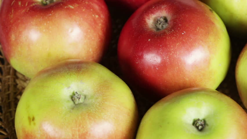 green and red apples in basket. shooting apples in basket on rotating table - hd stock footage clip green and red a
