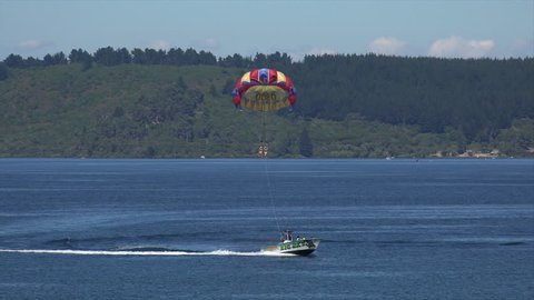 TAUPO, NORTH ISLAND/NEW ZEALAND - JANUARY 25, 2015: Unidentified people parasailing from boat, Lake Taupo. The lake is the largest freshwater lake in New Zealand.