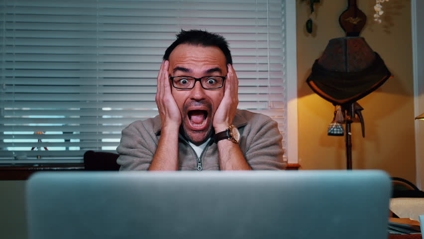 A shocked man looks at his laptop computer.  Looping.