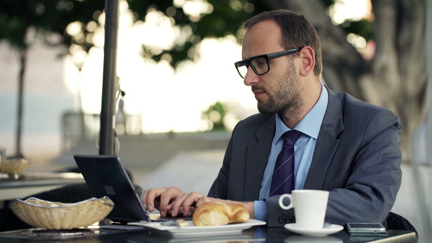 Handsome businessman working on laptop sitting in cafe in city