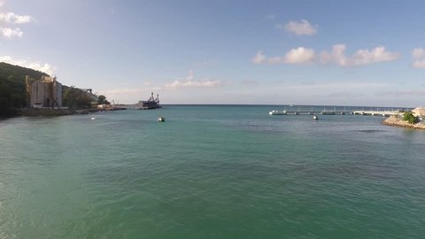 Aerial view of the bay in Jamaica in Ocho Rios. Hotels and resorts in the distance line the shoreline.