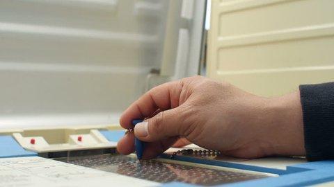 Voting, man's hand marking ballot