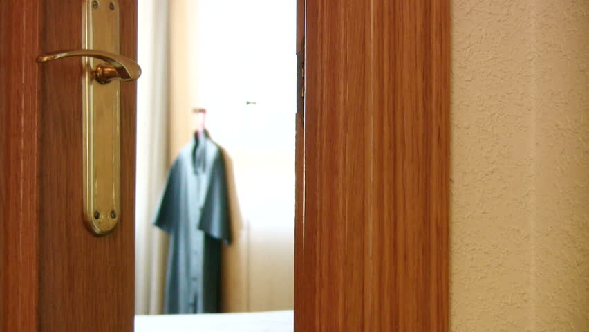"Man hangs ""Do Not Disturb"" sign on a hotel room door"