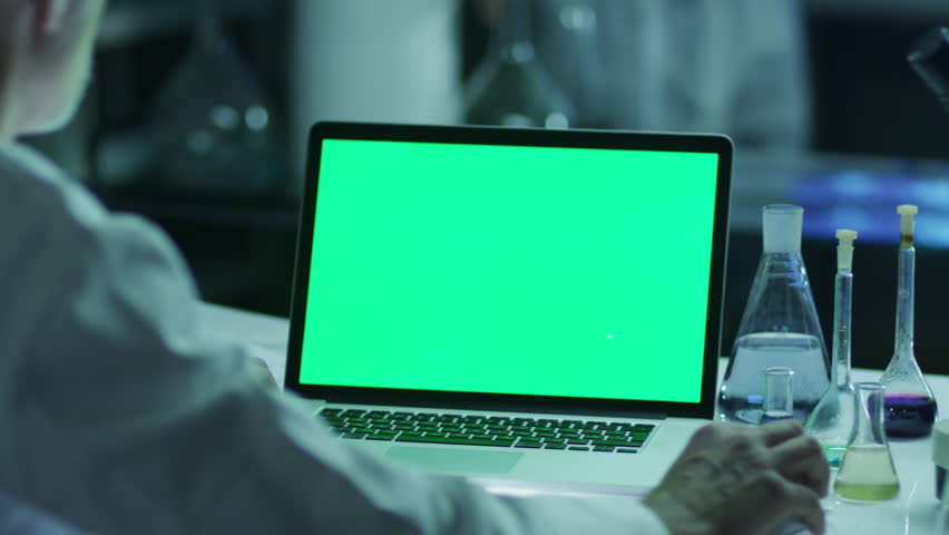 Scientist is using Laptop with Green Screen in Laboratory. Great for Mock-up Usage. Shot on RED Cinema Camera in 4K (UHD).   Shutterstock HD Video #9344909