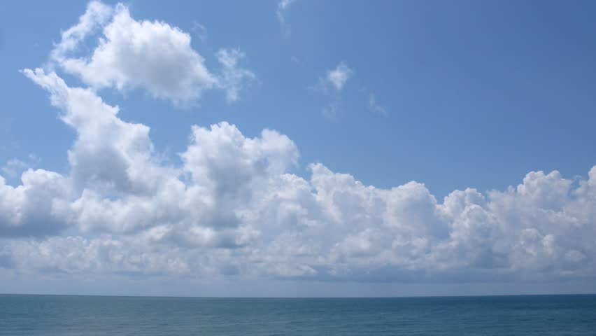 Sunny day on the sea, clouds move on the sky. Time lapse.