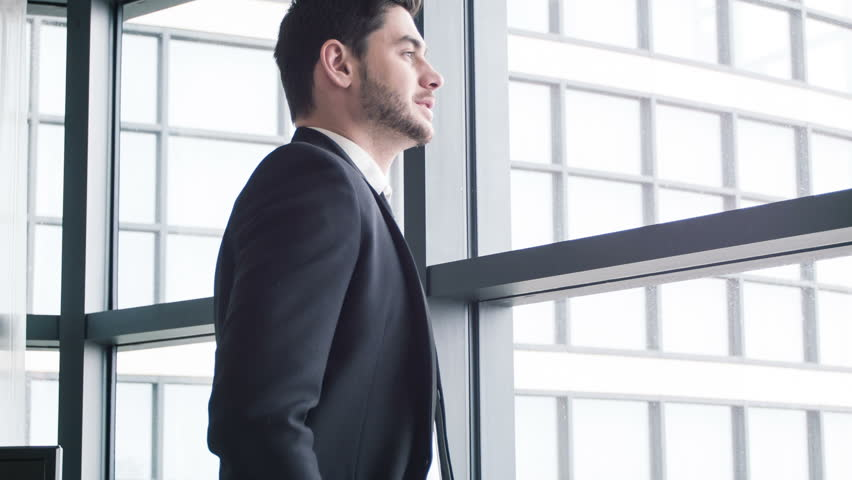 Confident and successful businessman. Handsome man in suit looking out of the window of business center