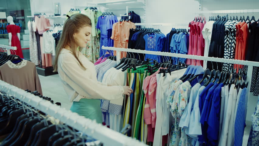 f618ccd0ffb Young girl in shop buying clothes. P. By ProCinemaStock. Stock footage ...
