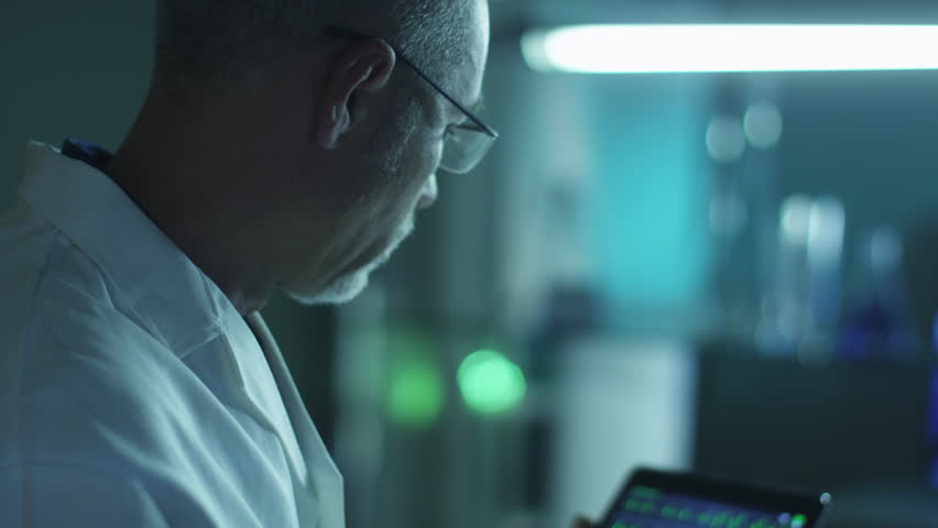Scientist is Checking Data on Tablet. Shot on RED Cinema Camera in 4K (UHD).