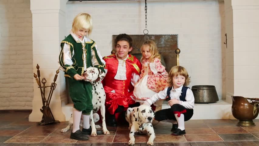 Happy father in medieval costume with three children and three dalmatians sit near chimney