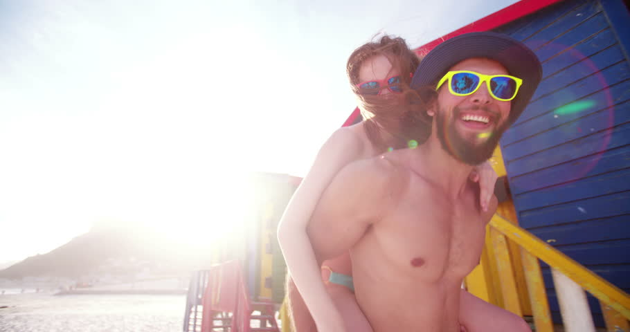 Cute young guy piggybacking his happy girlfriend in front of colourful beach huts in Slow Motion