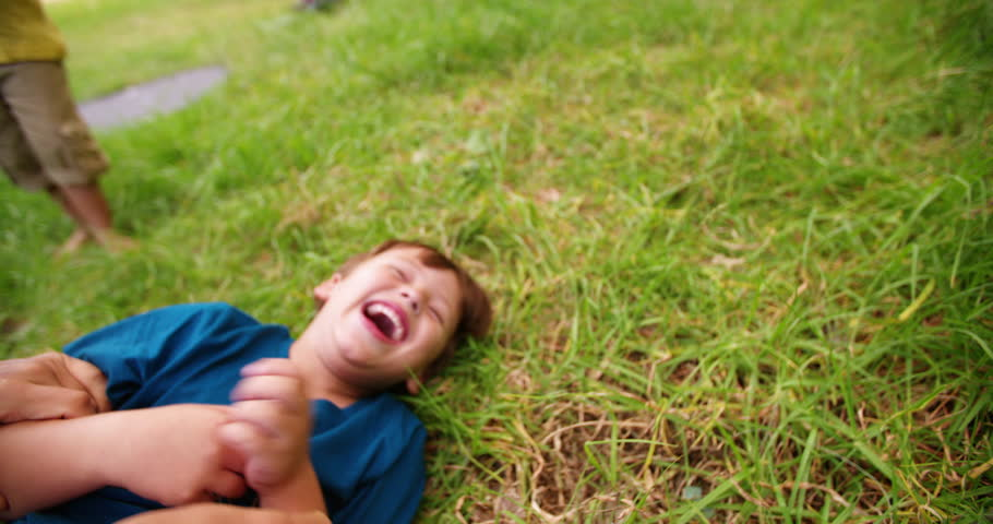 Happy boy laughing as he is being tickled lying on the grass