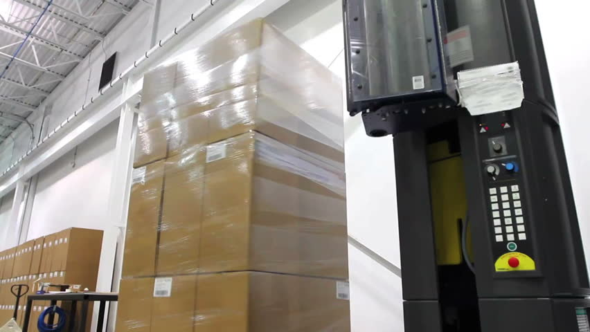 A shrink wrap machine covers a large stack of boxes