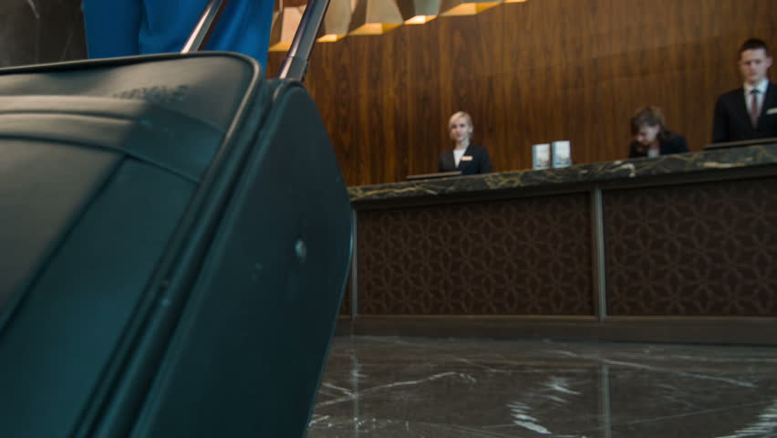 Arrival to hotel. New visitor with luggage coming to reception of five-star hotel to register and get key of his room  | Shutterstock HD Video #9449483