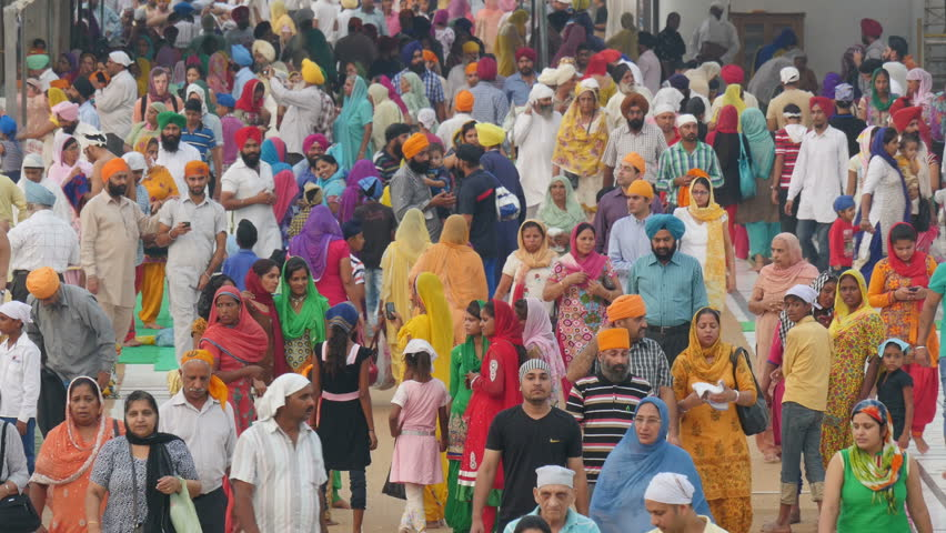 AMRITSAR, INDIA - 2 OCTOBER 2014: A colorful crowd walk around the Golden Temple complex in Amritsar. The Golden Temple is an important place for those who follow the Sikh religion.
